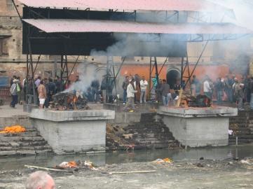 Liket bärs in på en bår av bambu, bränns och askan strös sedan ut i floden.